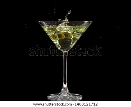 a glass of martini and a splash from falling olives #1488121712