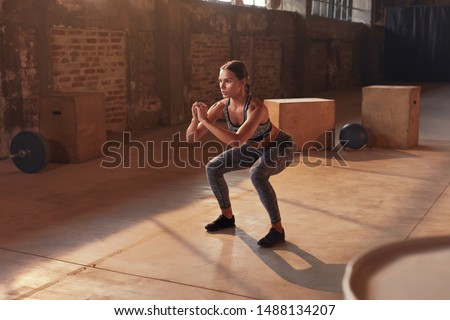 Fitness workout. Sport woman doing squat leg exercise at gym. Beautiful girl athlete with fit body in sportswear exercising, having functional training indoors Royalty-Free Stock Photo #1488134207