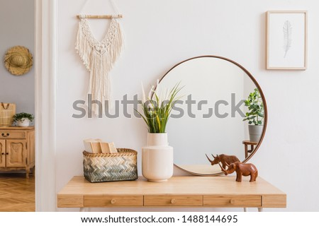 Sunny boho interiors of apartment with mirror, dressing table, furnitures, flowers, plants, rattan box, books, sculpture, macrame and design accessories. Stylish home decor of open space. Template. Royalty-Free Stock Photo #1488144695