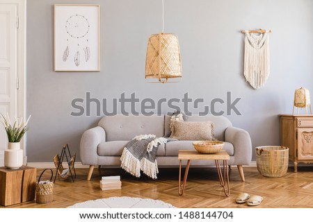 Stylish and design home interior of living room with gray sofa, wooden cube, commode, pillow, macrame, rattan lamp, basket, plants and elegant accessories. Stylish home decor. Template. Mock up poster Royalty-Free Stock Photo #1488144704