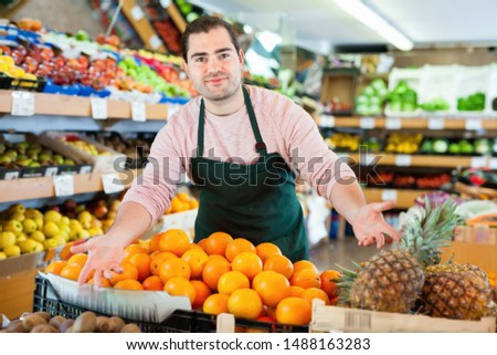 Young  cheerful positive smiling man in apron selling fresh oranges and fruits on the supermarket #1488163283
