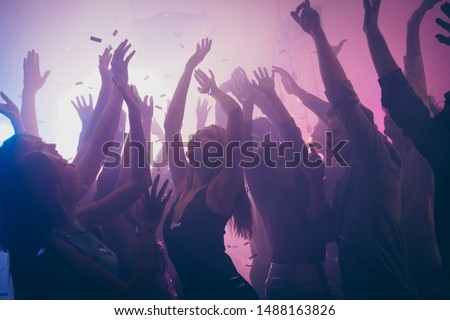 Photo of many birthday event people dancing purple lights confetti flying enjoy nightclub hands raised formal wear outfit #1488163826