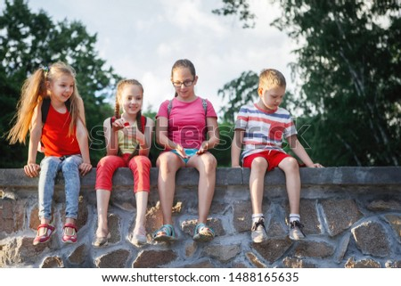 Brightly dressed teenagers sit in a group on a wall in a city park. Happy childhood, funny summer, child care. #1488165635