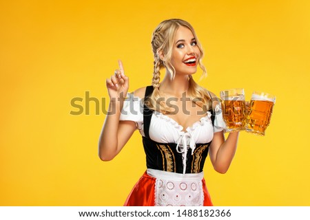 Young sexy Oktoberfest girl waitress, wearing a traditional Bavarian or german dirndl, serving big beer mugs with drink isolated on yellow background. Woman pointing to looking up. #1488182366