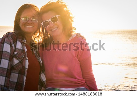 two cacuasian females friends at the beach with sunlasses sitting and posing hugged to the photo - beautiful sunset on the background - womans hugged and similing and looking at the camera #1488188018