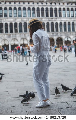 woman in white clothes with straw hat having fun with pigeons at venice city square piazza san marco