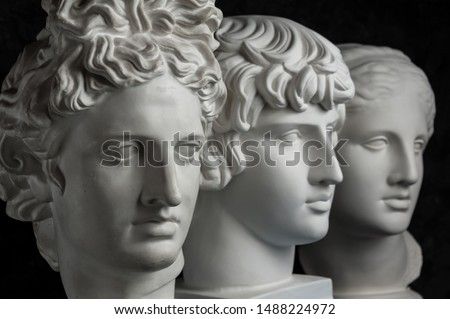 Gypsum copy of ancient statue Apollo, Antinous and Venus head on dark textured background. Plaster sculpture face. #1488224972