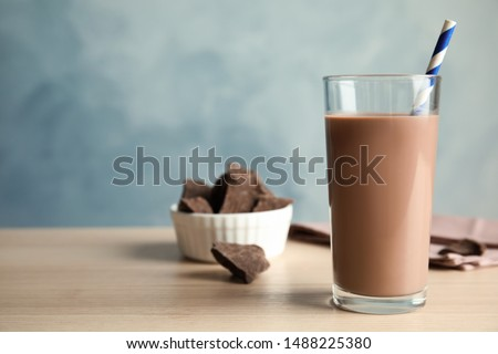 Glass of tasty chocolate milk on wooden table, space for text. Dairy drink #1488225380