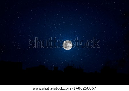 Silhouettes of skyscrapers different construction in the dark town with background of a large moon and clouds at nighttime. Royalty-Free Stock Photo #1488250067