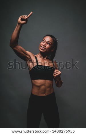 Portrait of healthy athletic 40 year old asian woman with a lean muscle and nice core body lifting her right arm and smiling with confident feeling of victory with the warm light and dark background. #1488295955