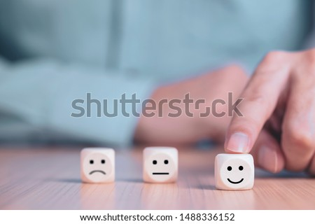 Businessman chooses a smile emoticon icons face happy symbol on wooden block , Services and Customer satisfaction survey concept #1488336152