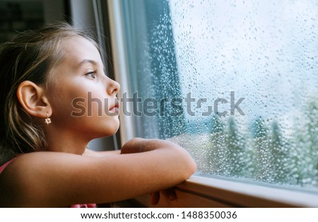 Little sad girl pensive looking through the window glass with a lot of raindrops. Sadness childhood concept image. #1488350036