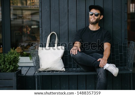 Young man holding white textile eco bag against urban city background. . Ecology or environment protection concept. White eco bag for mock up. #1488357359