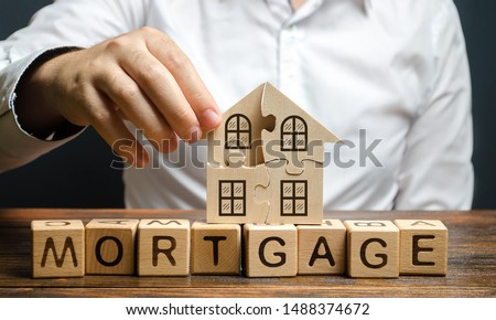 A man collects a house puzzle over the inscription Mortgage. Construction of your own residential building. Buying a home on credit loan, improvement of living conditions. Creating a family. #1488374672
