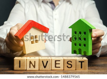 Wooden blocks with the word Invest, and houses in the hands of a businessman. The concept of investing in real estate construction. Effective investment. Buying apartments. Business and finance #1488379565