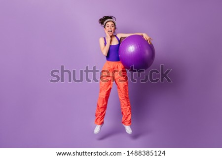 Girl in high spirits jumps with fitball on purple background. Portrait of lady in multi-colored sports suit #1488385124