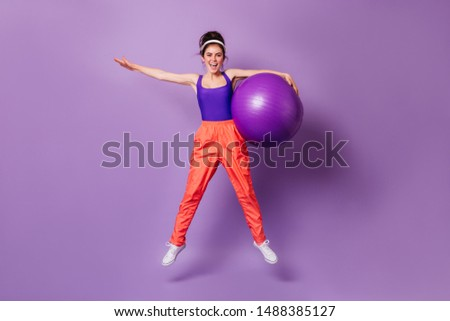 Adorable dark-haired woman in bright sports outfit doing exercises. Girl in cap jumps with purple fitball #1488385127