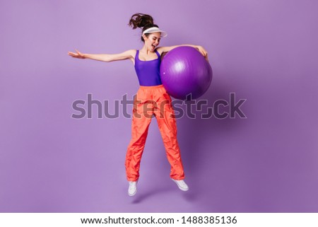 Full-length portrait of sportswoman with fitball in her hands. Young brunette girl wearing cap jumping on purple background #1488385136
