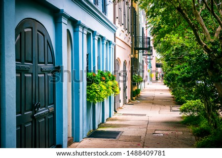 Empty sidewalk view of lush summer greenery lining the colorful Georgian architecture of the colonial Rainbow Row in the historical Battery neighborhood of Charleston, South Carolina, USA Royalty-Free Stock Photo #1488409781