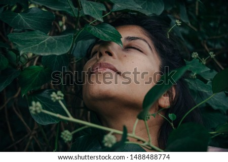 Portrait of beautiful woman eyes closed, peacefully surrounded by green leaves. Connection with nature concept. Sierra de la Ventana, Argentina, circa october 2018 #1488488774