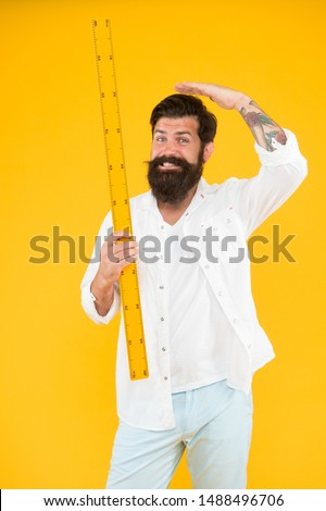 Measuring his height with ruler. School teacher or university student holding ruler on yellow background. Bearded man taking measurements with metric ruler. My ruler is longer than yours. #1488496706