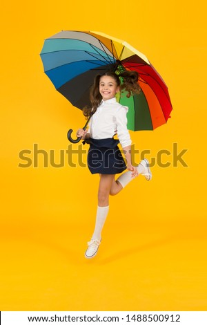 Back to school on September 1. Adorable schoolgirl with rainbow umbrella on September 1 on yellow background. Small child going to school on September 1. Little girl at first school day, September 1. #1488500912