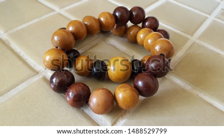 A macro shot of some African wooden beads. The beads are dark brown and light brown.  #1488529799