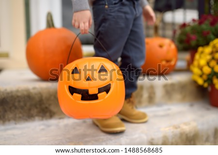Little boy at halloween celebrations party. Child holds a bucket shaped like a halloween pumpkin jack o lantern. Halloween - traditional american holiday. #1488568685