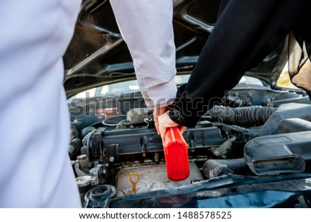 Arabic woman and her husband pouring oil in the car engine #1488578525