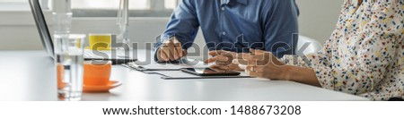 Wide view image of male and female business partners working together sitting at office desk reviewing reports and paperwork while alsousing digital tablet. Royalty-Free Stock Photo #1488673208