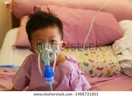 Asian boy got Bronchitis and used bronchodilator in hospital. Kid in hospital. Sick child. Boy using asthma machine. #1488731801