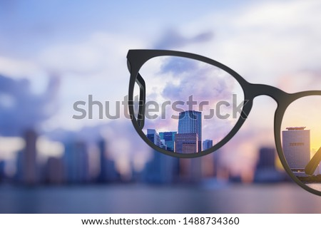Modern bright city view through eyeglasses. Blurry background. Vision concept Royalty-Free Stock Photo #1488734360