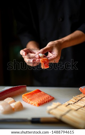 Closeup of chef hands preparing japanese food. Japanese chef making sushi at restaurant. Young chef making  traditional japanese sushi on cuting board . #1488794615
