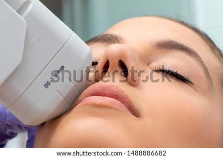 Extreme close up of HIFU treatment on female face. Therapist doing cosmetic plasma lift with high intensity focal ultrasound device. #1488886682