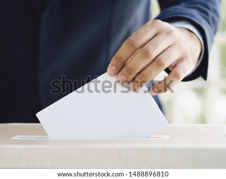 Man putting an empty ballot in election box #1488896810