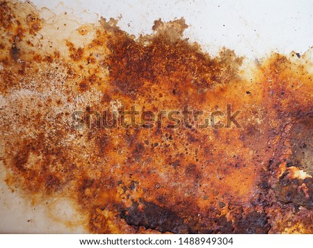Brown, black and yellow rust on white enamel. Rusted brown and white abstract texture. Corroded white metal background. Rusted white painted metal wall. Rusty metal surface with streaks of rust.  #1488949304