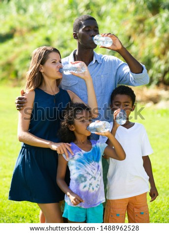 Happy mixed race family with two children enjoying walk on green meadow, drinking clear water #1488962528