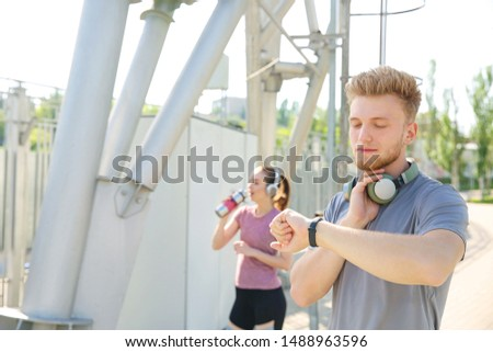 Sporty young man checking his pulse outdoors #1488963596