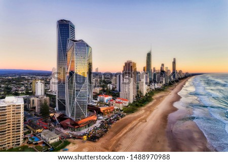Reflecting facets of modern urban high-rise towers on Australian Gold Coast in Queensland Surfers Paradise. Wide sandy long beach of Pacific shore at sunrise in elevated aerial view along waterfront. Royalty-Free Stock Photo #1488970988