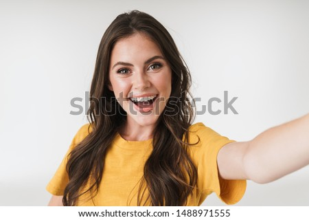 Image of caucasian brunette woman wearing casual t-shirt smiling and looking at camera while taking selfie photo isolated over white background