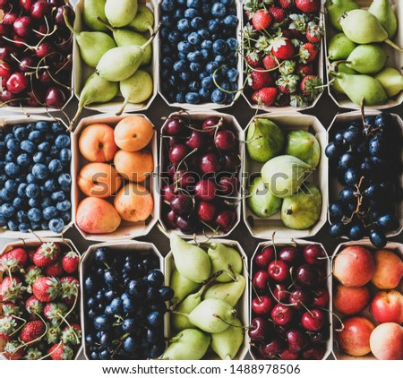 Summer fruit and berry assortment. Flat-lay of strawberries, cherries, grapes, blueberries, pears, apricots, figs in eco-friendly boxes over grey background, top view, close-up. Local farmers produce #1488978506