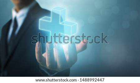 Businessman hand holding plus sign virtual means to offer positive thing (like benefits, personal development, social network) #1488992447