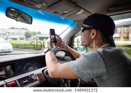 Men who drive a car while looking at the smartphone #1489001372