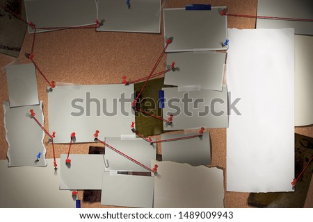 Detective board with photos of suspected criminals, crime scenes and evidence with red threads