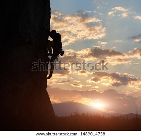 Side view of strong rock climber at dawn. Male silhouette on high rocky wall having extreme outdoors activity. Concept of perseverance and never give up. Sunrise sky with clouds and copy space #1489014758