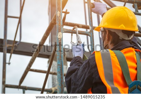 [safety body construction] Working at height equipment. Fall arrestor device for worker with hooks for safety body harness on selective focus. Worker as in construction background. #1489015235
