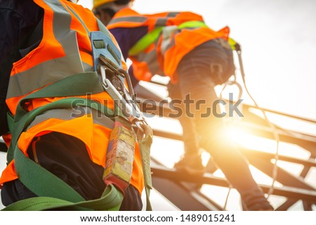[safety body construction] Working at height equipment. Fall arrestor device for worker with hooks for safety body harness on selective focus. Worker as in construction background. #1489015241
