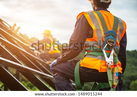 [safety body construction] Working at height equipment. Fall arrestor device for worker with hooks for safety body harness on selective focus. Worker as in construction background. #1489015244