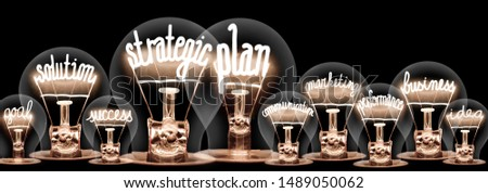 Group of light bulbs with shining fibers in a shape of Strategic Plan, Solution, Success and Idea concept related words isolated on black background #1489050062