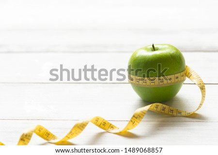 Diet and Healthy life loss weight exercise Concept. Green apple and Weight scale measure tap with fresh vegetable prevention for women diet slimming.  Lifestyle and Healthy   #1489068857